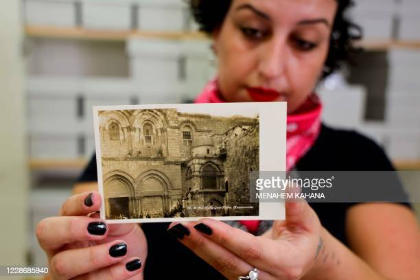 """Sachar Knaani, a researcher at the Hebrew University, holds laminated postcards from the """"Postcards of Palestine"""" collection at the university in..."""