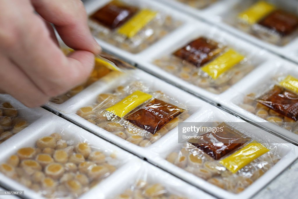 Sachets of seasoning sauce and mustard are arranged atop polystyrene trays of fermented soybeans, known as natto, at the Matsushita Shoten Y.K. production facility in Kawasaki, Kanagawa Prefecture, Japan, on Friday, June 7, 2013. From Japan's natto makers and operators of neighborhood baths to its largest refiner and utilities, the weaker yen offers domestically focused industries nothing to offset higher import prices. Photographer: Kiyoshi Ota/Bloomberg via Getty Images