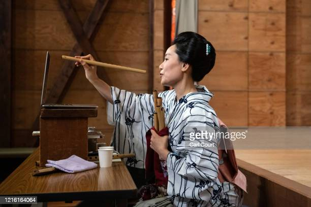 Sachika originally from Yokohama and a geisha for 20 years holds a flute to the webcam as she entertains clients online via Zoom on May 29 2020 in...