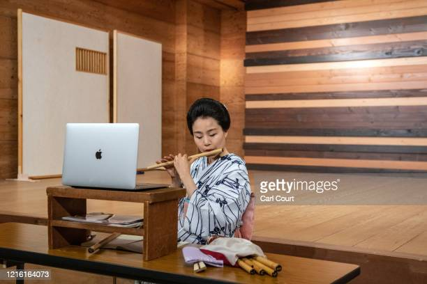 Sachika originally from Yokohama and a geisha for 20 years plays a flute as she entertains clients online via Zoom on May 29 2020 in Hakone Japan A...