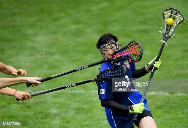 Sachiko Komine of Japan is challenged by Sophie Whitehead and Olivia Wimpenny of Great Britain during the Lacrosse Women's match between Great...