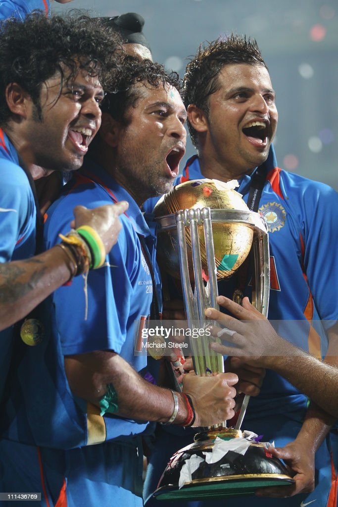 Sachin Tendulkar (C) of India alongside Shanthakumaran Sreesanth (L) and Suresh Raina (R)with the winners trophy after the six wicket win during the 2011 ICC World Cup Final between India and Sri Lanka at Wankhede Stadium on April 2, 2011 in Mumbai, India.