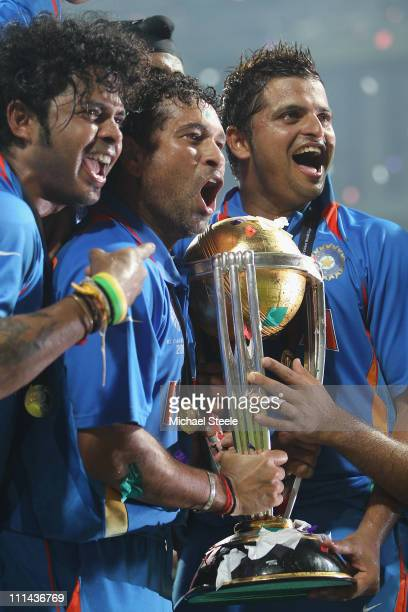 Sachin Tendulkar of India alongside Shanthakumaran Sreesanth and Suresh Raina with the winners trophy after the six wicket win during the 2011 ICC...