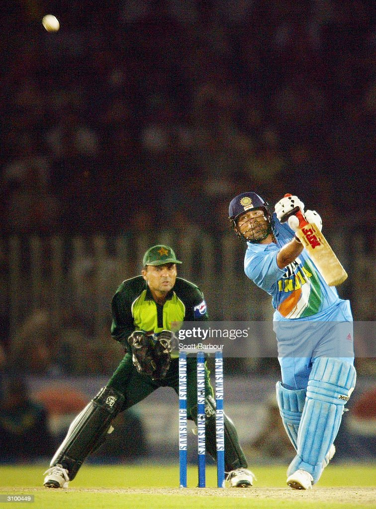 Sachin Tendulkar (R) of India hits out during his innings of 141 as wicketkeeper Moin Khan of Pakistan watches during the second Pakistan v India one day international match played at Pindi Cricket Stadium March 16, 2004 in Rawalpindi, Pakistan.