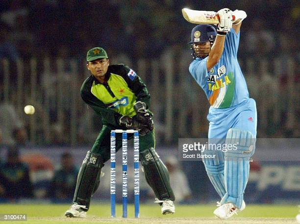Sachin Tendulkar of India hits out during his innings of 141 as wicketkeeper Moin Khan of Pakistan watches during the second Pakistan v India one day...
