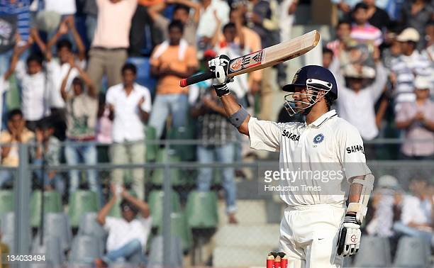 Sachin Tendulkar of India raises his bat after completing his halfcentury during the third day of the third test match between India and West Indies...
