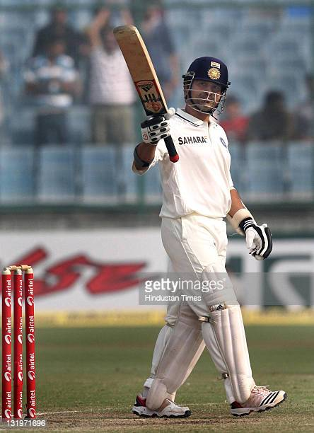 Sachin Tendulkar of India raises his bat after scoring his 62nd test halfcentury during the fourth day of the first test match between India and West...