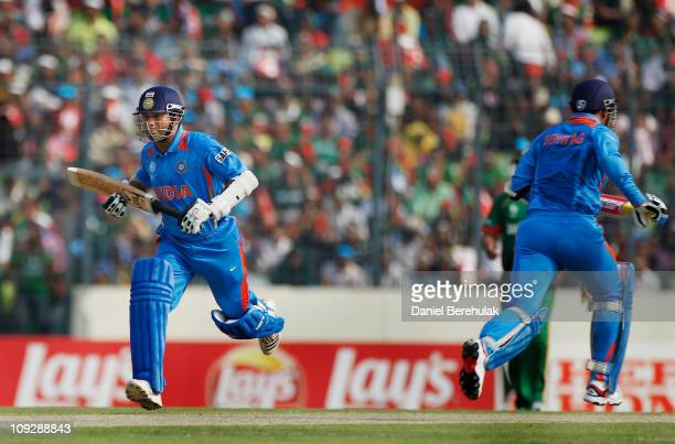 Sachin Tendulkar of India runs between wickets with thea mate Virender Sehwag during the opening game of the ICC Cricket World Cup between Bangladesh...