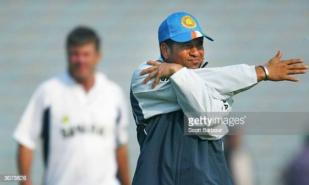 Sachin Tendulkar of India stretches while being watched by coach John Wright before the Pakistan 'A' v India warm-up match March 11, 2004 in Lahore,...