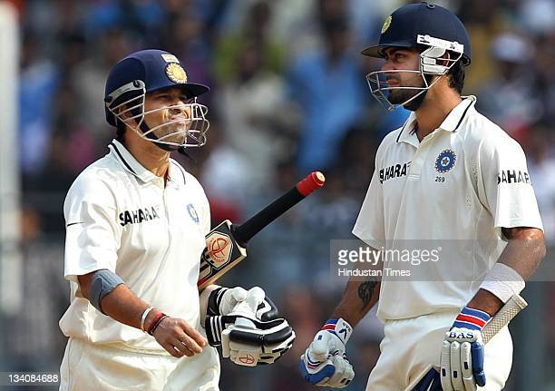 Sachin Tendulkar of India walks past by teammate Virat Kohli after getting out for 94 runs during the fourth day of the third test match between...