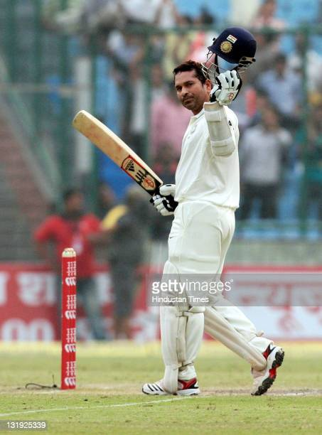Sachin Tendulkar raises his bat and helmet after completing 15000 runs in test cricket highest ever by any batsman during the third day of the first...