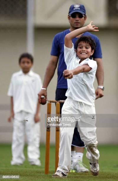Sachin Tendulkar's son Arjun bowling in a friendly match among his friends as Sachin Tendulkar stands as a umpire on the eve of his birthday at the...
