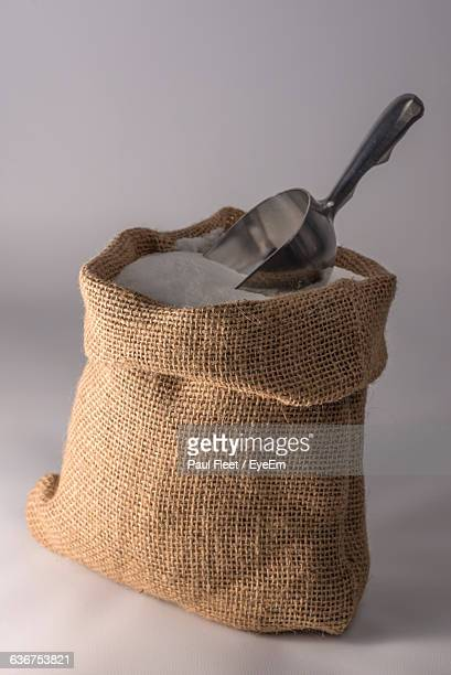 Sack Of Flour With Spoon Against White Background