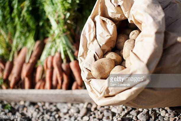 Sack of potatoes and crate of carrots