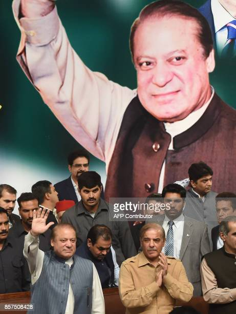 Sacked Pakistani prime minister Nawaz Sharif gestures as his brother Chief Minister of Punjab province Shahbaz Sharif claps his hands during the PMLN...