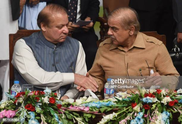 Sacked Pakistani prime minister Nawaz Sharif shakes hands with his brother and Chief Minister of Punjab province Shahbaz Sharif during the PMLN...