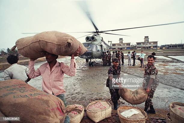 Sacks and baskets of food are unloaded from an army helicopter for distribution to island farmers who have just survived one of the biggest cyclones...