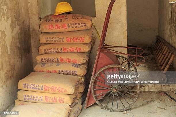 Sacks of cement and wheelbarrow, Nanfeng Kiln, Foshan, China