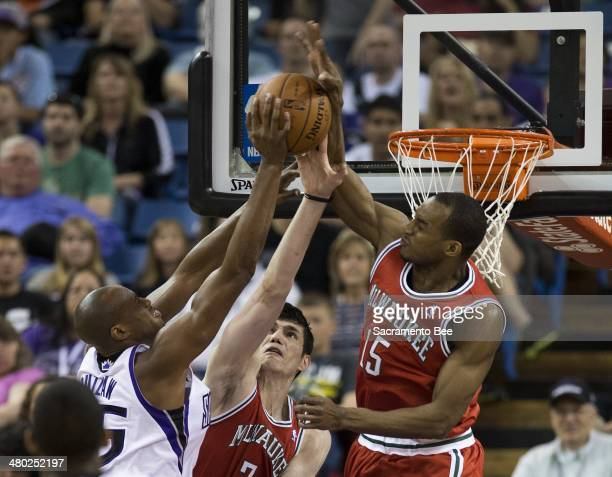 Sacramento Kings forward Travis Outlaw has his shot blocked by Milwaukee Bucks forward Chris Wright and Milwaukee Bucks forward Ersan Ilyasova at...