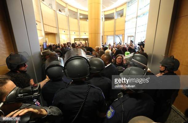 Sacramento police officers in riot gear bloclk the entrance to a city council meeting at Sacramento City Hall on March 27 2018 in Sacramento...