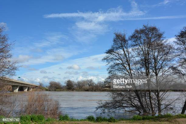 sacramento river near flood stage with the hamilton city bridge to the side. - swift river fotografías e imágenes de stock