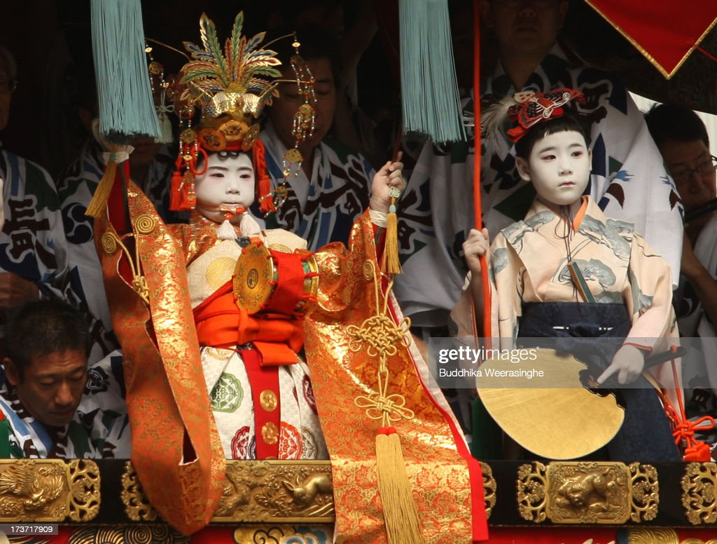 A sacred child (L) performs a ritual on float named Yamahoko during the annual Kyoto Gion Festival on July 17, 2013 in Kyoto, Japan. The Gion festival is one of three biggest Japanese festivals. dating back to the 9th century, the festival is part of a ritual intended to satisfy the Gods that brought on fire, floods and earthquakes. During the festival the streets are decorated with lanterns and many of the women dress in 'yukata', summer kimonos.