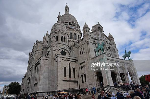 Sacred Heart Basilica of Montmartre in Paris on a background of partly blue, partly overcast sky, in early fall . The basilic is seen from the front...