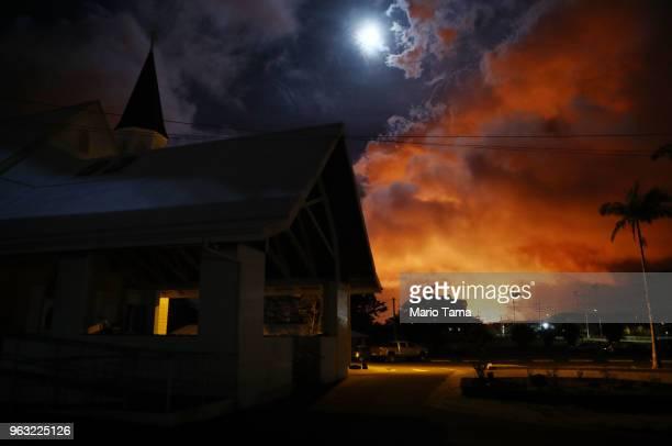 Sacred Heart Church Pahoa stands as lava from a Kilauea volcano fissure illuminates the night sky and volcanic gases rising , on Hawaii's Big Island,...