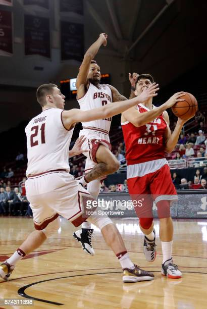 Sacred Heart forward Mario Matasovic goes to the hoop defended by Boston College guard Ky Bowman and Boston College forward Nik Popovic during a game...