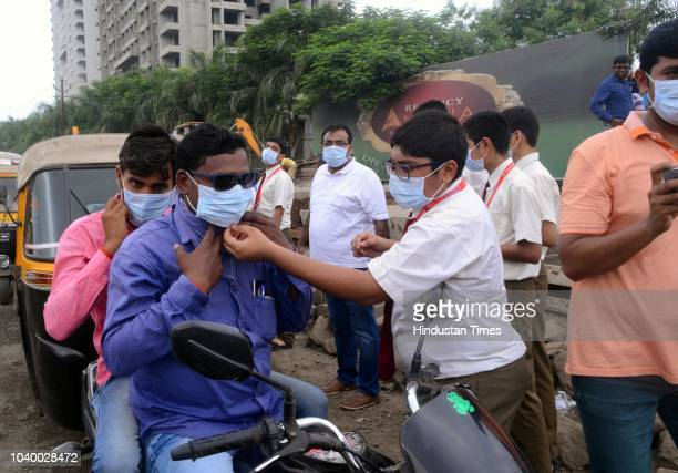 Sacred Heart School students distribute face masks to fight air pollution caused by the ongoing road work at Kalyan Shahad road on September 24 2018...