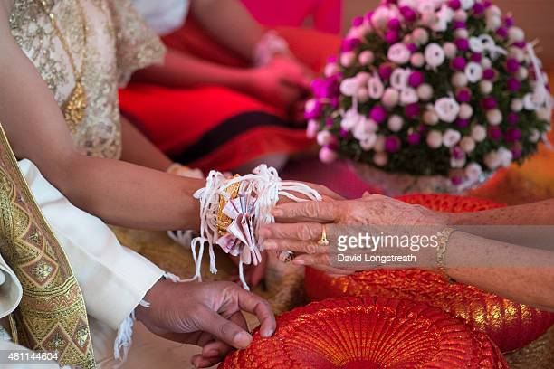 Sacred string is tied to the wrist of Kanokporn and Montri Thi during ceremonies at their wedding in Ta Par Mok Thailand Thai Buddhist marriage...