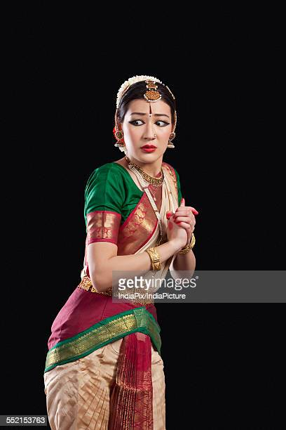 Sacred woman performing classical dance on black background