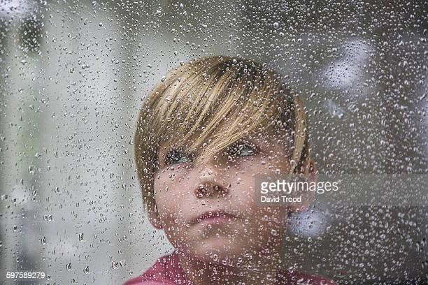 Sad 15 yr old boy looking through window.