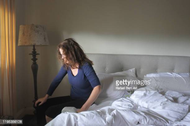sad adult woman sitting on bed confused and exhausted - rafael ben ari stock-fotos und bilder