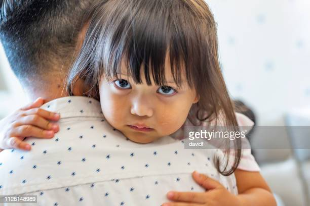sad and crying daughter being comforted by her father - sad child stock pictures, royalty-free photos & images