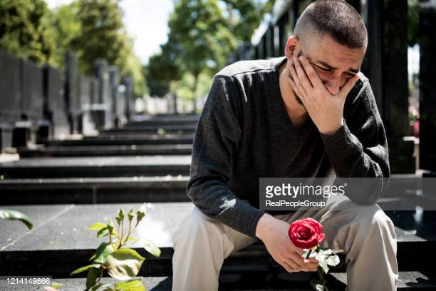 sad and depressed widower in black clothes kneeling in front of the headstone, holding a flower and moaning for family loss. concept for death, mourning, funeral and spirituality.- covid-19 - dead stock pictures, royalty-free photos & images