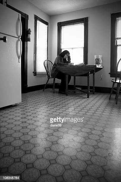 Triste et solitaire femme assise sur le kitchen table