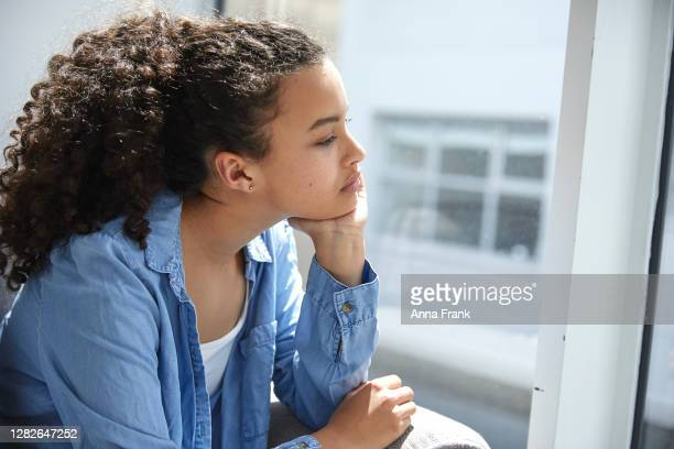 sad and unhappy teenager looking out of the window - sadgirl stock pictures, royalty-free photos & images