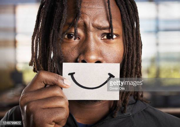 sad, anxious man holding smiling card over his mouth - funny racist of black people stock pictures, royalty-free photos & images