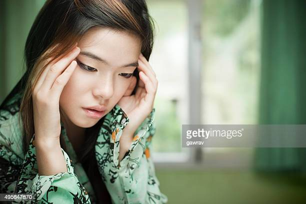 Sad Asian cute girl sitting near window holding her head.