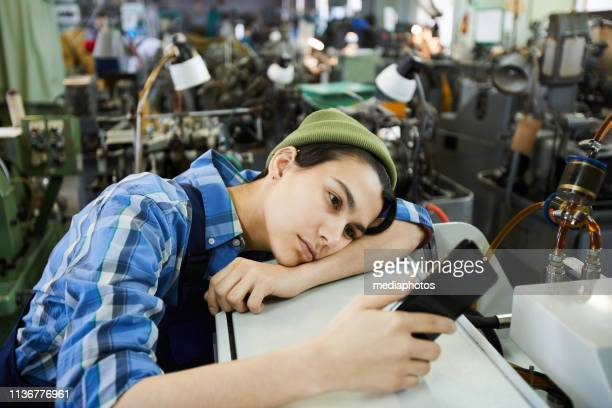 sad attractive young woman worker in beanie hat being bored at workplace, she using smartphone and leaning on industrial equipment - wasting time stock pictures, royalty-free photos & images