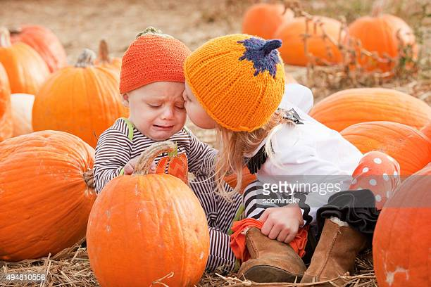 Sad Baby Brother Getting Kiss From Sister In Pumpkin Patch