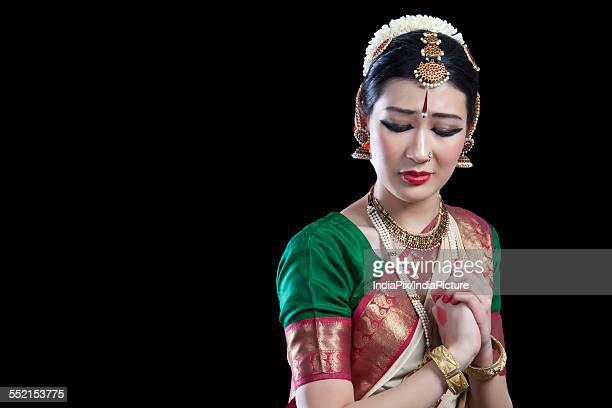 Sad Bharatanatyam dancer performing over black background