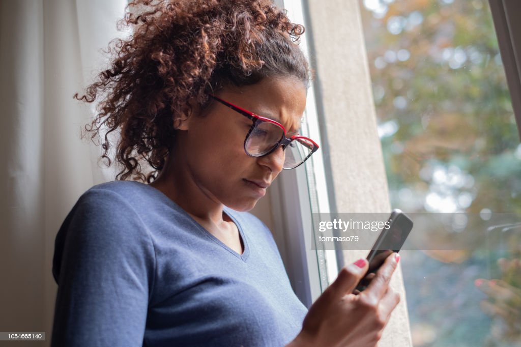 Sad black woman near window reading phone message : Stock Photo