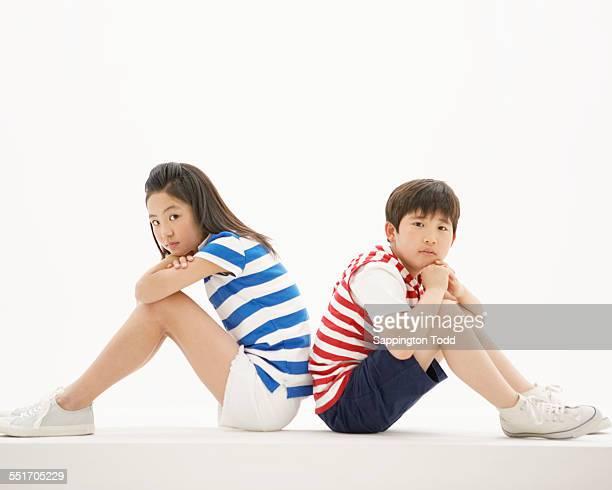 Sad Boy And Girl Sitting Back To Back