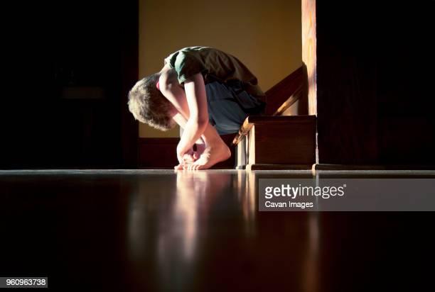 Sad boy hugging knees while sitting on steps
