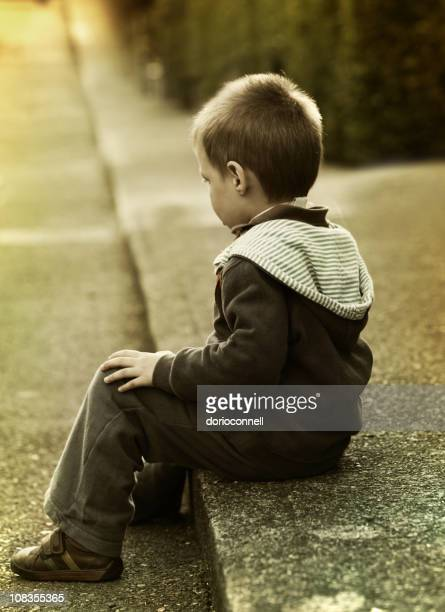traurige junge - straßenrand stock-fotos und bilder