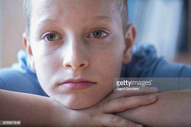 sad boy resting head on arms, freiburg im breisgau, baden-w��rttemberg, germany - sigrid gombert stockfoto's en -beelden