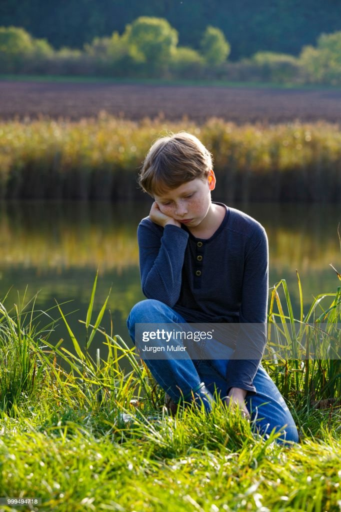 Sad boy sitting on a small lake, Wandersleben, Thuringia, Germany : Stock Photo