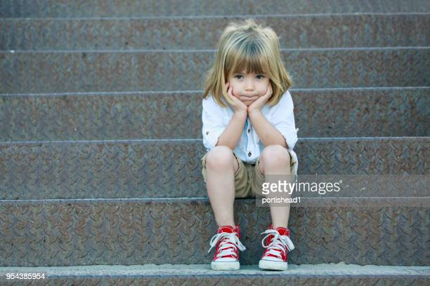 sad boy sitting on staircase - sitting stock pictures, royalty-free photos & images